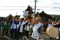 集会所を出発する神輿の一行。市長の顔も見える
