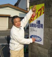 ポスターをブロック塀に貼り出す