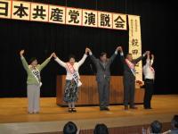 聴衆からの拍手にこたえる穀田衆院議員(真ん中)ら
