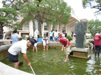 噴水の池をきれいにする市民たち